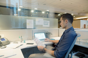Focused businessman working late at laptop in cubicleの写真素材 [FYI02282222]