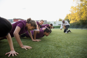 Physical education teacher encouraging students doing push-upsの写真素材 [FYI02282303]