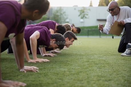 Physical education teacher encouraging students doing push-upsの写真素材 [FYI02282424]