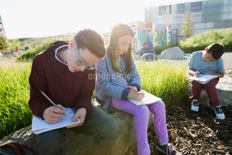 Students doing homework on rocks at sunny playgroundの写真素材 [FYI02282426]