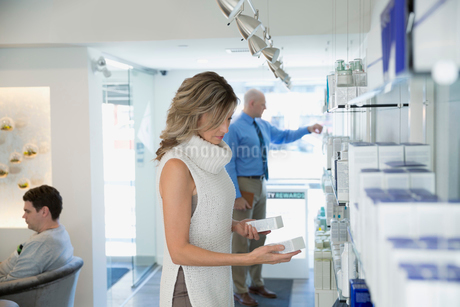 Woman browsing products in esthetician office lobbyの写真素材 [FYI02282517]