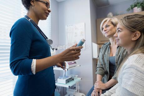 Pediatrician explaining inhaler to patient and motherの写真素材 [FYI02282526]