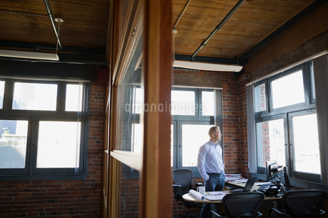 Pensive businessman looking out office windowの写真素材 [FYI02282597]