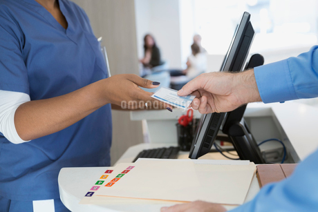 Patient giving nurse medical identification card in clinicの写真素材 [FYI02282607]