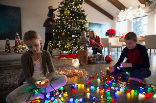 Brother and sister untangling Christmas tree string lightsの写真素材 [FYI02282706]