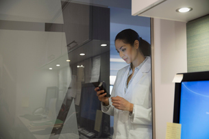Doctor texting at glass wall in clinicの写真素材 [FYI02282714]