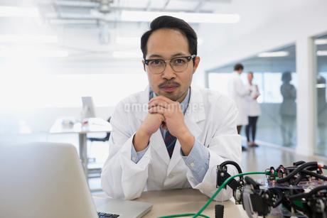 Portrait confident engineer at laptop near roboticsの写真素材 [FYI02282743]