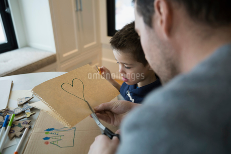 Father and son cutting out heart-shapeの写真素材 [FYI02282837]