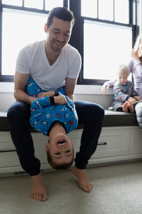 Father holding laughing son upside-downの写真素材 [FYI02282958]