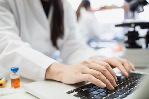 Medical scientist typing on laptop in laboratoryの写真素材 [FYI02283004]