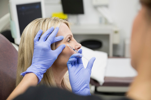 Technician giving woman botox injection corner of eyeの写真素材 [FYI02283017]