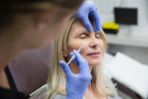 Technician giving woman botox injection side of noseの写真素材 [FYI02283035]