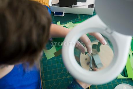 Craftswoman assembling diorama under magnifying lampの写真素材 [FYI02283120]