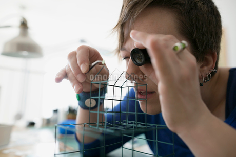 Craftswoman using loupe to assemble wire cageの写真素材 [FYI02283130]
