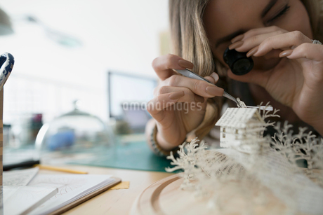 Craftswoman using loupe to assemble paper dioramaの写真素材 [FYI02283175]