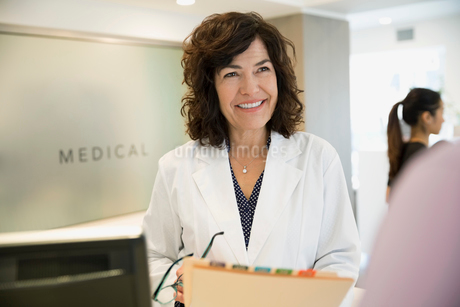 Smiling female doctor with medical record clinic receptionの写真素材 [FYI02283283]