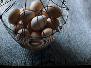 Fresh organic chicken eggs in wire basketの写真素材 [FYI02283305]