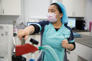 Veterinarian using equipment in clinic operating roomの写真素材 [FYI02283436]