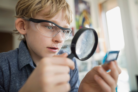 Boy with magnifying glass examining computer chipの写真素材 [FYI02283448]