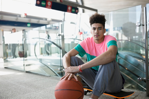 Portrait confident young man basketball skateboard train stationの写真素材 [FYI02283475]