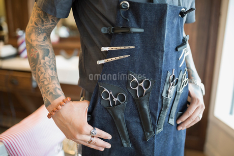 Midsection tattooed barber wearing apron with toolsの写真素材 [FYI02283482]