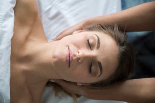 Serene woman with eyes closed receiving head massageの写真素材 [FYI02283500]