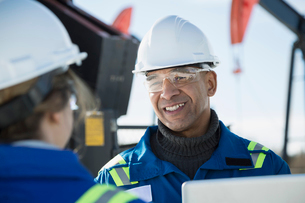 Smiling engineer talking to coworker at gas plantの写真素材 [FYI02283626]