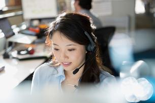 Businesswoman wearing headset at desk in officeの写真素材 [FYI02283658]