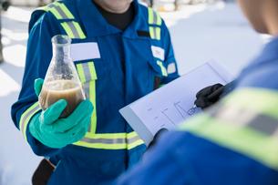 Engineers testing recording liquid in beaker gas plantの写真素材 [FYI02283669]