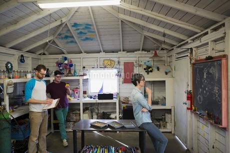 Glassblowers brainstorming at blackboard in workshopの写真素材 [FYI02283679]