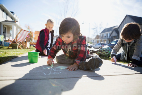 Kids drawing on sidewalk with chalkの写真素材 [FYI02283736]