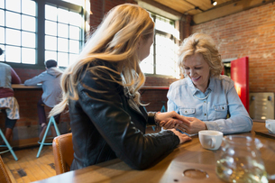 Daughter showing mother engagement ring in coffee shopの写真素材 [FYI02283789]