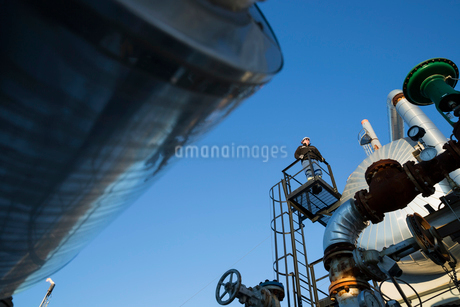 Male engineer standing on platform above gas plantの写真素材 [FYI02283825]