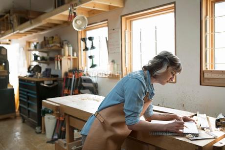Female carpenter brainstorming and sketching in workshopの写真素材 [FYI02283919]