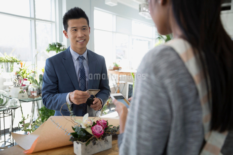 Man paying florist for bouquet in flower shopの写真素材 [FYI02284072]