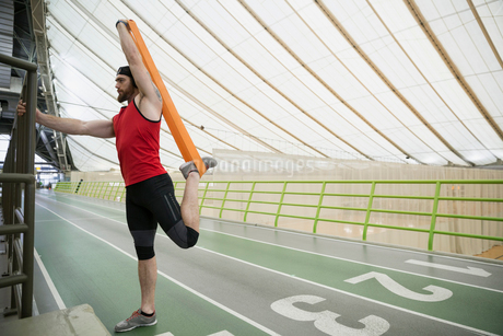 Runner stretching leg with resistance band indoor trackの写真素材 [FYI02284108]