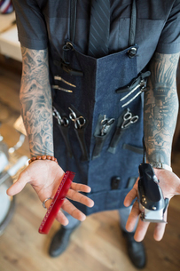 Midsection tattooed barber wearing apron with toolsの写真素材 [FYI02284175]