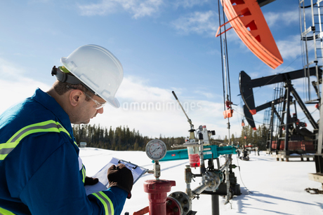 Male worker with clipboard examining drilling rig gaugeの写真素材 [FYI02284208]
