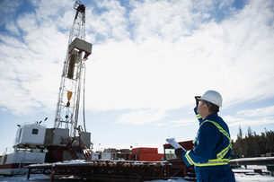Male engineer looking up drilling rig gas plantの写真素材 [FYI02284219]
