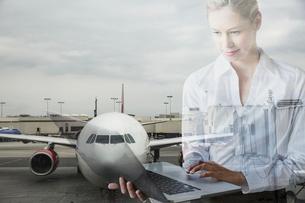 Digital composite businesswoman using laptop against airplane tarmacの写真素材 [FYI02284287]