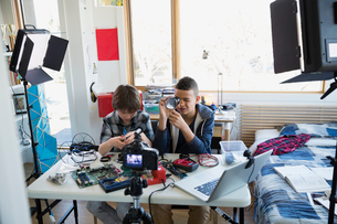 Boys videotaping circuit board assembly in bedroomの写真素材 [FYI02284304]
