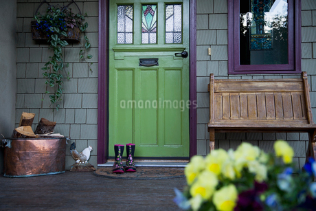 Rubber boots on welcome mat at green painted doorの写真素材 [FYI02284417]