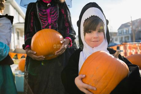 Portrait boy in whale Halloween costume holding pumpkinの写真素材 [FYI02284524]