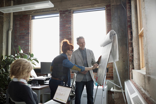Business people brainstorming at flipchart in officeの写真素材 [FYI02284538]