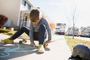 Boy on skateboard drawing on sidewalk with chalkの写真素材 [FYI02284634]