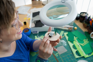 Craftswoman assembling diorama under magnifying lampの写真素材 [FYI02284805]