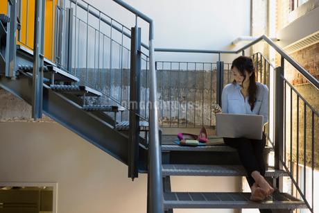 Barefoot businesswoman texting and using laptop on staircaseの写真素材 [FYI02284869]