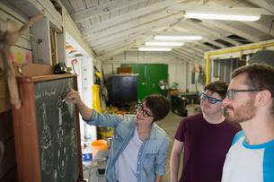 Glassblowers brainstorming at blackboard in workshopの写真素材 [FYI02284878]