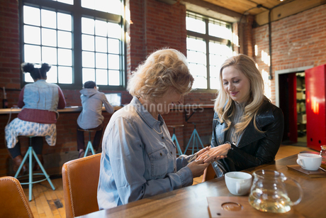 Daughter showing mother engagement ring in coffee shopの写真素材 [FYI02285074]