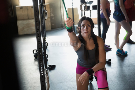 Focused woman using resistance band at gymの写真素材 [FYI02285115]